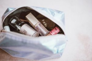 Open, shiny makeup bag containing budget drugstore makeup and beauty products