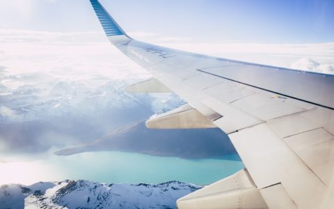 White flight wing flying over clouds, mountains and blue sea