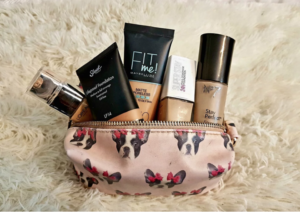 Liquid foundations popping out of an opened, pink makeup bag