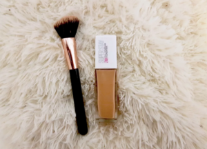 Maybelline 24 hour superstay foundation with makeup brush on a fluffy white background