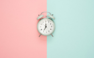 Alarm clock to remember to drink water on pink and blue background