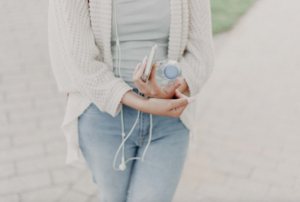 Girl holding earphones and a bottle of water to drink