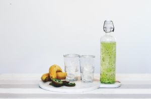 A bottle of green drink to drink with glasses and fruits on the side