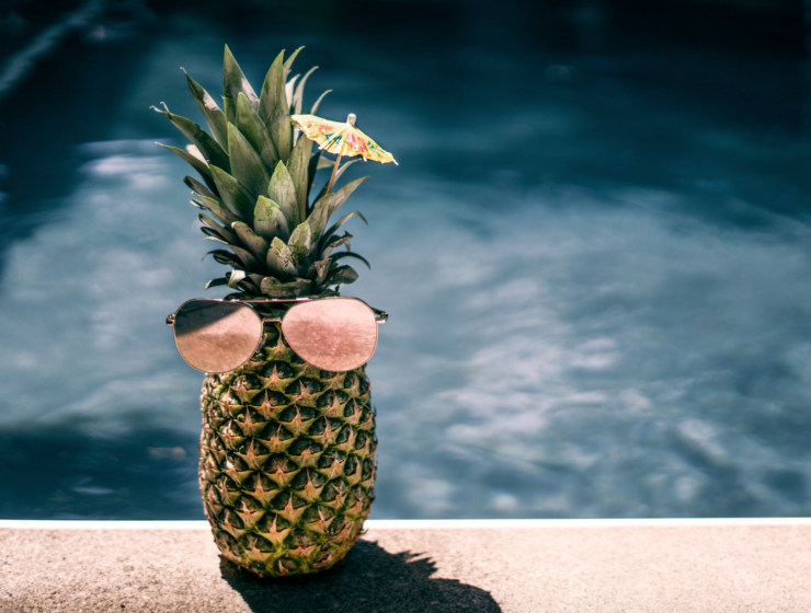 Pineapple with sunglasses on by the pool in the summer