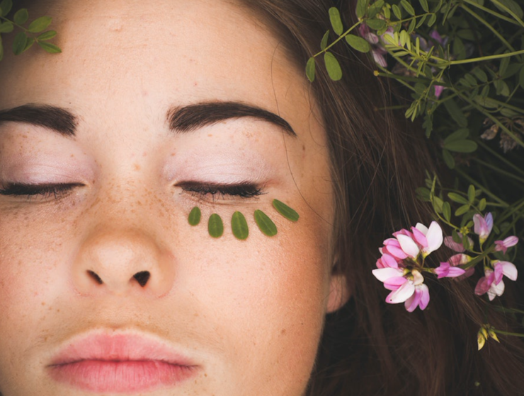 Girl laying in grass with flowers with green makeup under her eyes