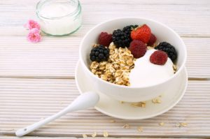 Oatmeal for facial popsicles with berries and yogurt in white bowl and spoon on the side