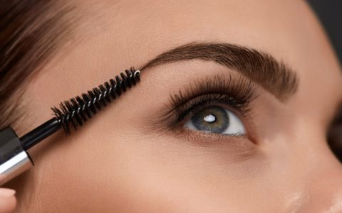 close up of womans eye area, brushing her eyebrow with a brush wand.