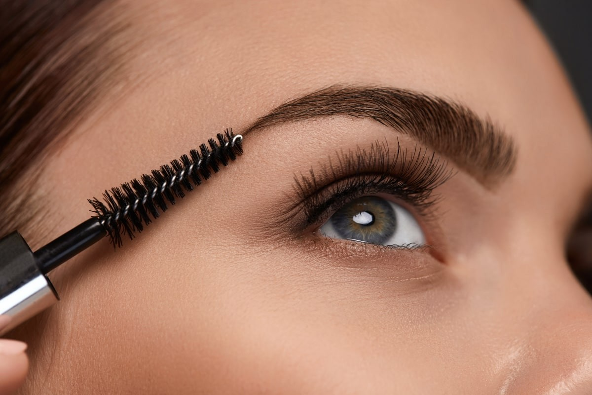 close up of womans eye area, brushing her Eyebrows with a brush wand.