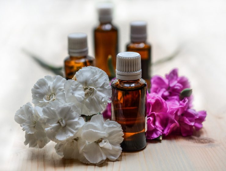 Bottles of facial oil with pink and white flowers