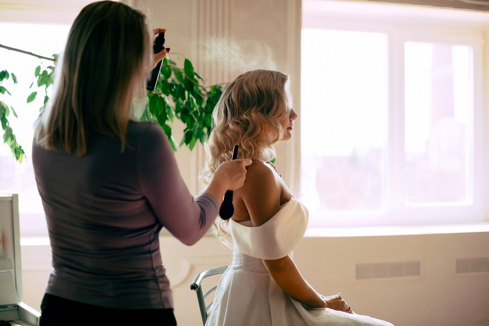 hair stylist spraying a lady's hair whilst preparing her for an event.