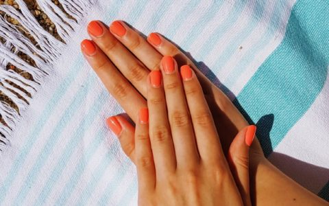 lady's hands on a beach towel, upon sand, painted orange.