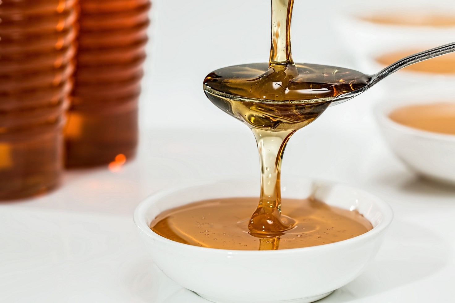 raw honey being poured onto a spoon and overflowing into a white bowl below.