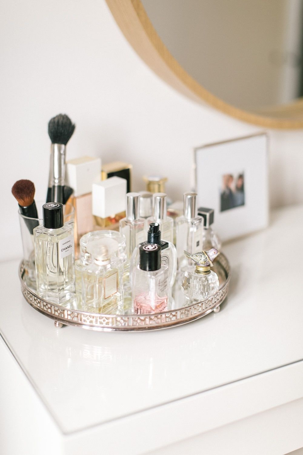 a collection of perfume bottles on a mirrored silver tray on a shiny white desk.