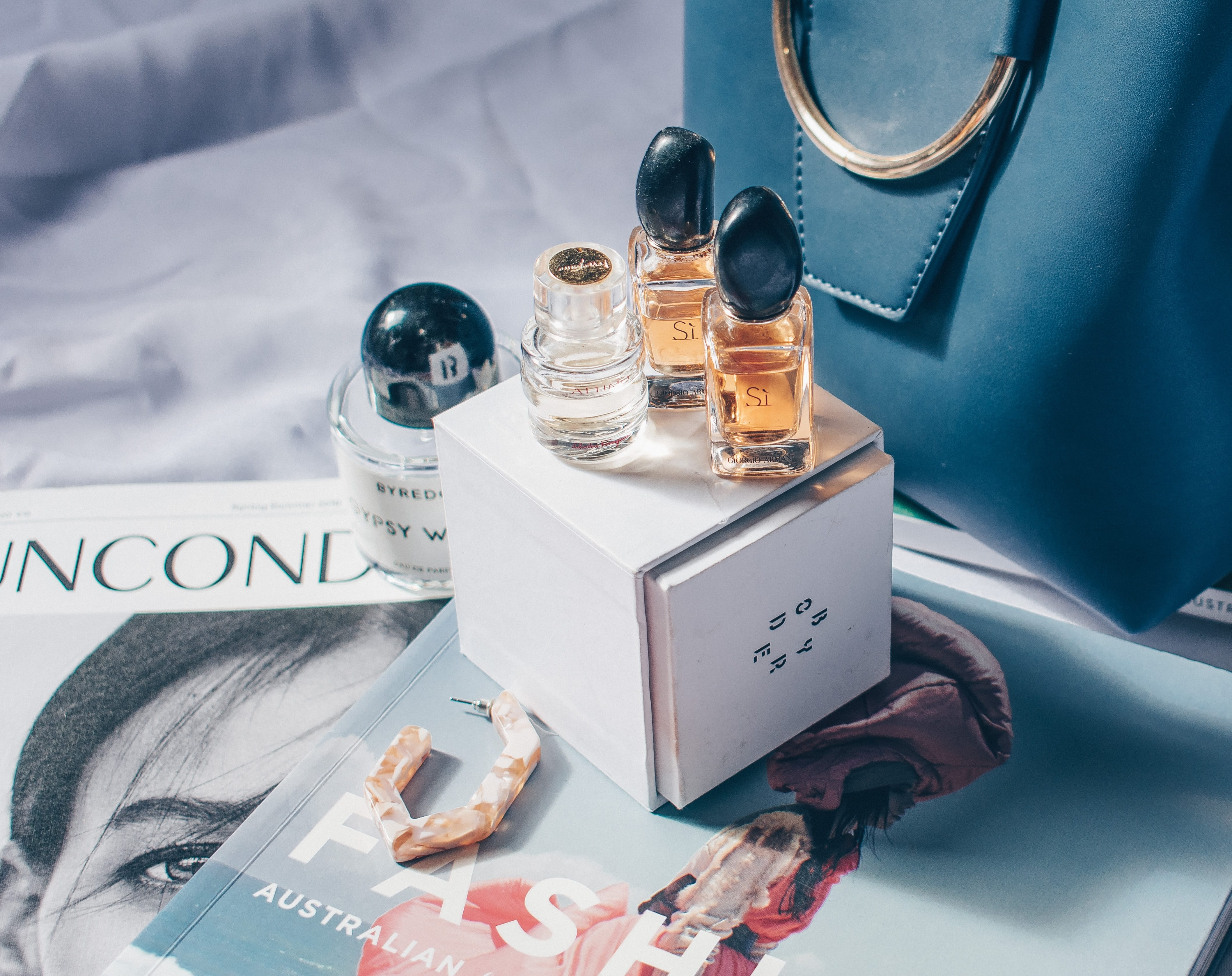 Miniature perfume bottles on top of a white box beside a sprawl of magazines.