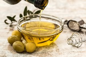 A bottle of natural olive oil being poured into a clear bowl with olives on the side of it