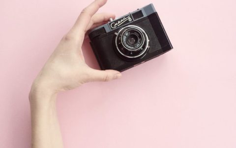 hand holding camera for taking photos on pink background