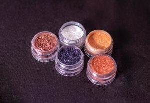 Colorful glitter makeup in plastic pots