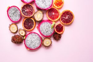 Lots of exotic, sliced fruits on pink background