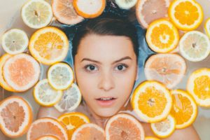 Lady lying in a natural bath full of lemons, limes and oranges