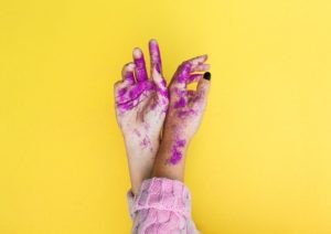 Pink glitter makeup on girl's hands on yellow background