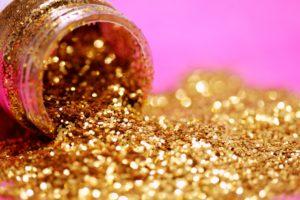 Gold glitter makeup pot spilling glitter on pink background