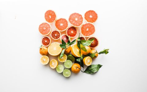 A variety of citrus fruit to treat acne scars including orange, lemon and lime on a white background