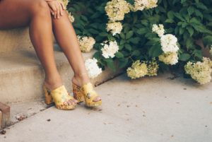 Woman's legs sitting on step near flowers with yellow shoes after hair removal