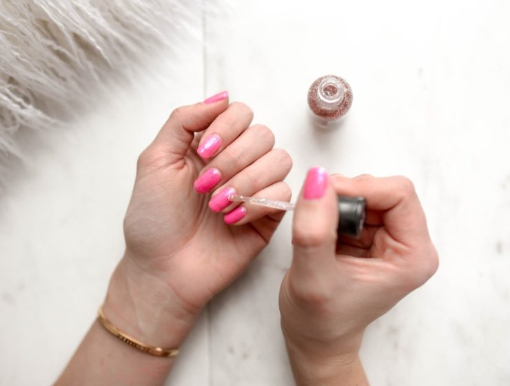 Lady applying pink nail polish to her fingernails on a white, tile floor
