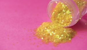 Gold glitter makeup spilling from plastic pot on pink background
