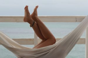 Hair removal, hair free legs with anklet on a white hammock near the sea