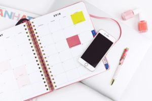 planner open with phone and pen nearby to make a schedule for hair removal