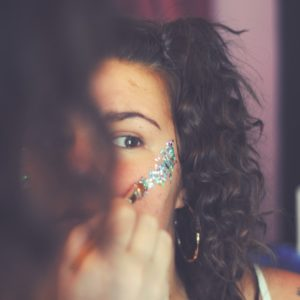 Lady applying glitter makeup to cheeks with makeup brush