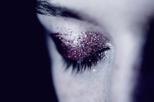 Lady with purple glitter makeup on eyelid