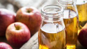 Bottles of natural apple cider vinegar with apples on the side
