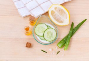 Natural ingredients including aloe vera and cucumber, essential oils and salt in a brown background