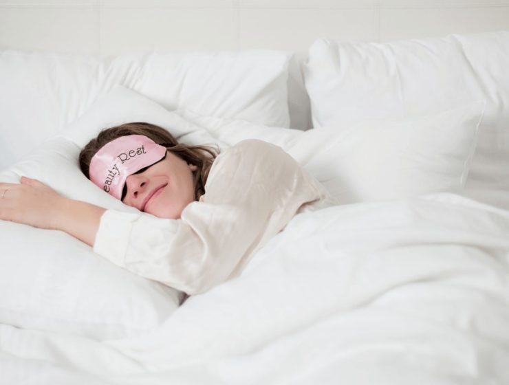 woman sleeping with face mask on over her eyes on white bedding.