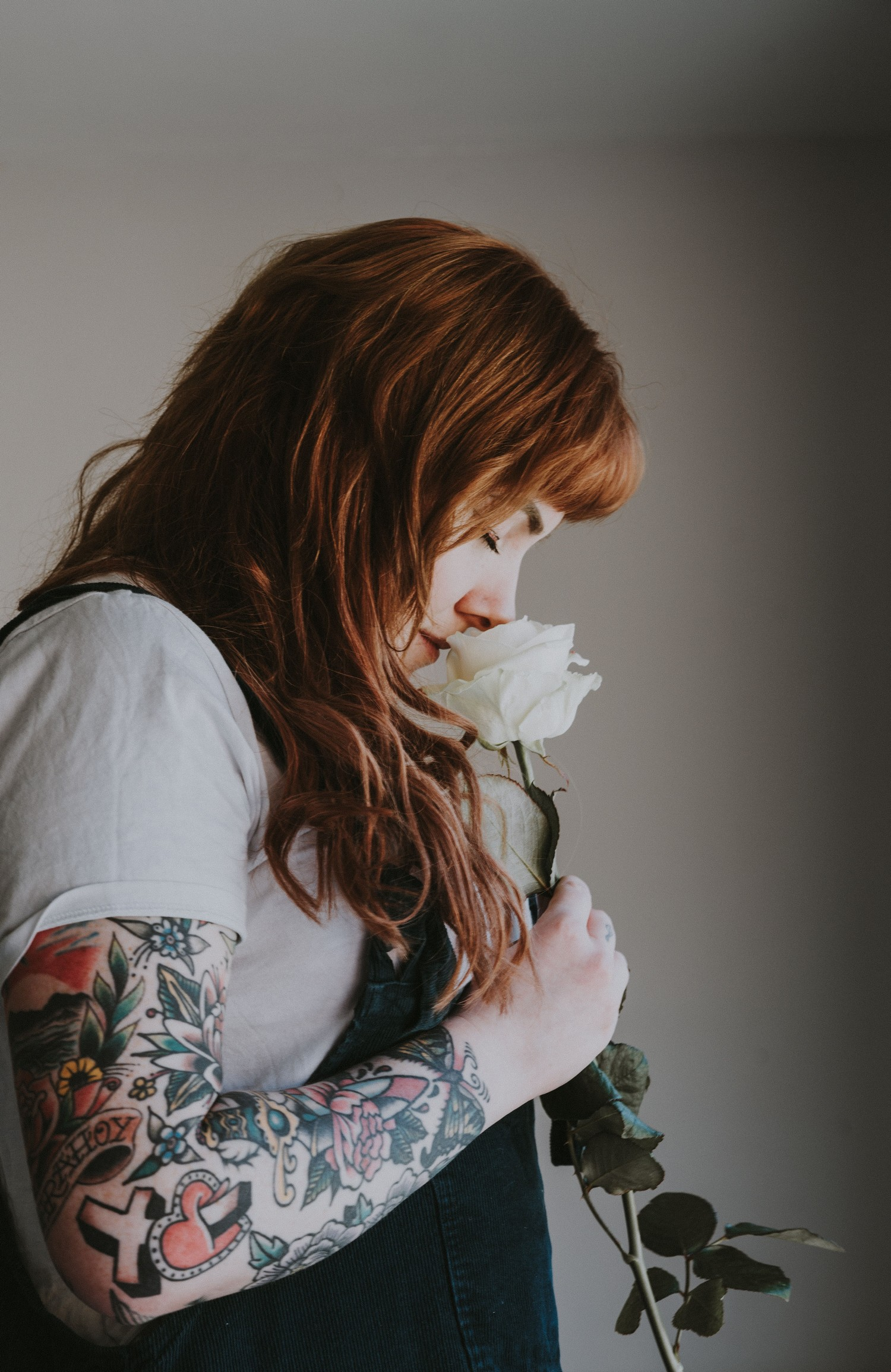 a red-haired woman holding a white flower, whilst smelling it.
