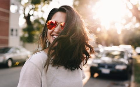 it's summer: woman, wearing sunglasses, smiling whilst stood on the pavement, with trees and blurred sunshine behind her.