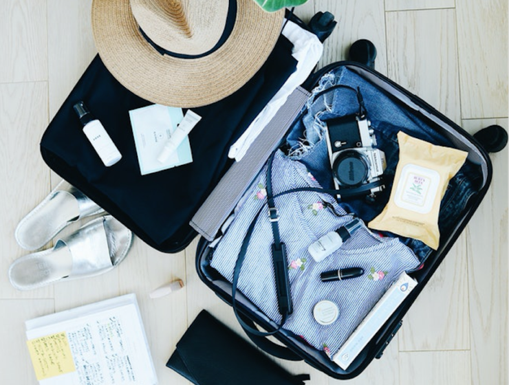 Pack open suitcase with clothe and cosmetics scattered around
