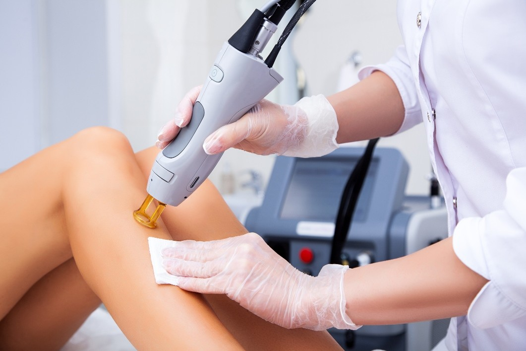a professional carrying out laser hair removal on woman's legs.
