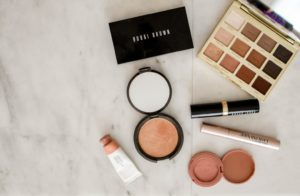Makeup products on marble table that are easy to pack for flight