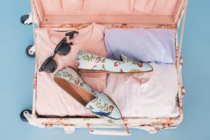 Pack open floral suitcase with folded clothes and sunglasses inside