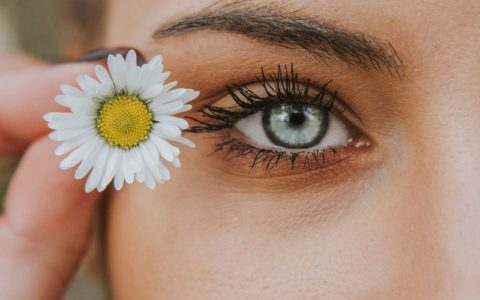 Woman holding a daisy flower to her eye