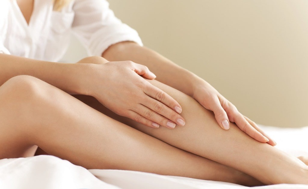 a woman's legs, with her hand on her knee.