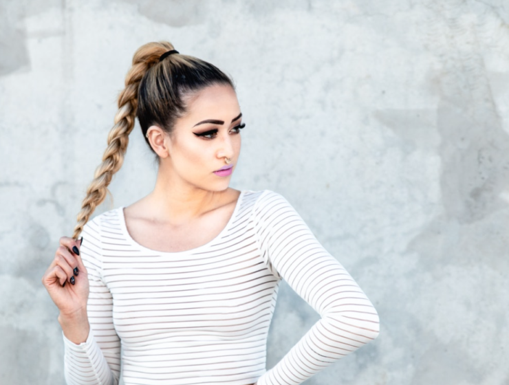 Woman wearing makeup and holding her hair as she poses