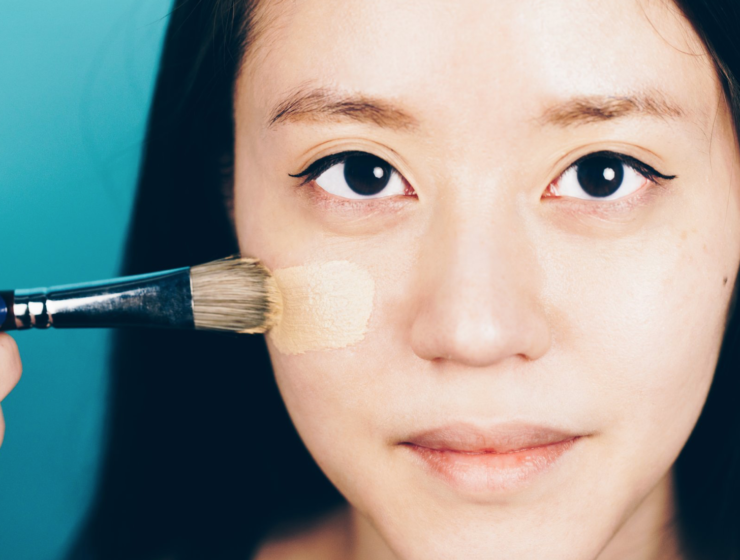 Woman applying foundation with brush to her face