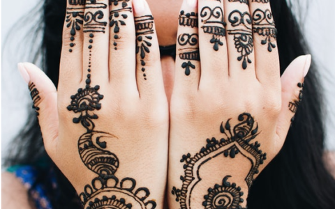 Woman covering her face with henna on her hands