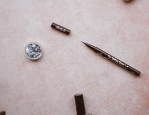 an open eyeliner pen on a pink surface