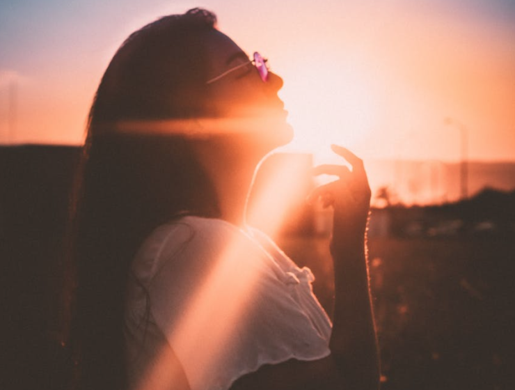 Woman standing exposed to the sun wearing sunglasses during sunset
