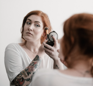 Woman applying powder to her face in a compact mirror
